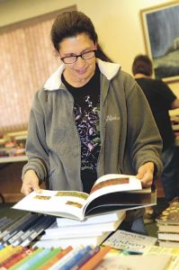 Staff photo: Tony Bullocks Nancy Fischer of Clovis takes time Friday afternoon to buy some books at the Friends of the Library book sale at the Clovis-Carver Public Library. Fischer said she loves to read and non-fiction is what she likes the most. The sale continues to day from 9 a.m. to 4 p.m.