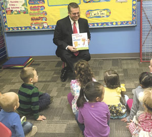 Staff photo: Brooke Finch Curry County Manager Lance Pyle reads a book to preschoolers at Clovis Nazarene School on Monday as part of the county's Imagination Library reading program.