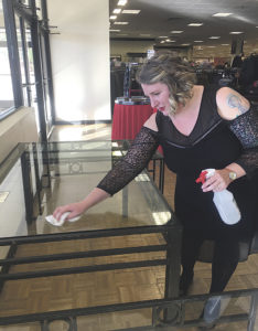 Staff photo: Brooke Finch Stephanie Shirley, Dillard's area sales manager in Clovis, cleans a display table in preparation for arranging merchandise to entice shoppers for Black Friday.