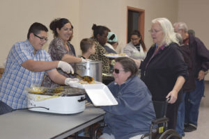 Staff photo: Alisa Boswell Luis Cruz, 13, left, serves a local resident some sweet potatoes Thursday during the Portales community Thanksgiving dinner at the Memorial Building in Portales.
